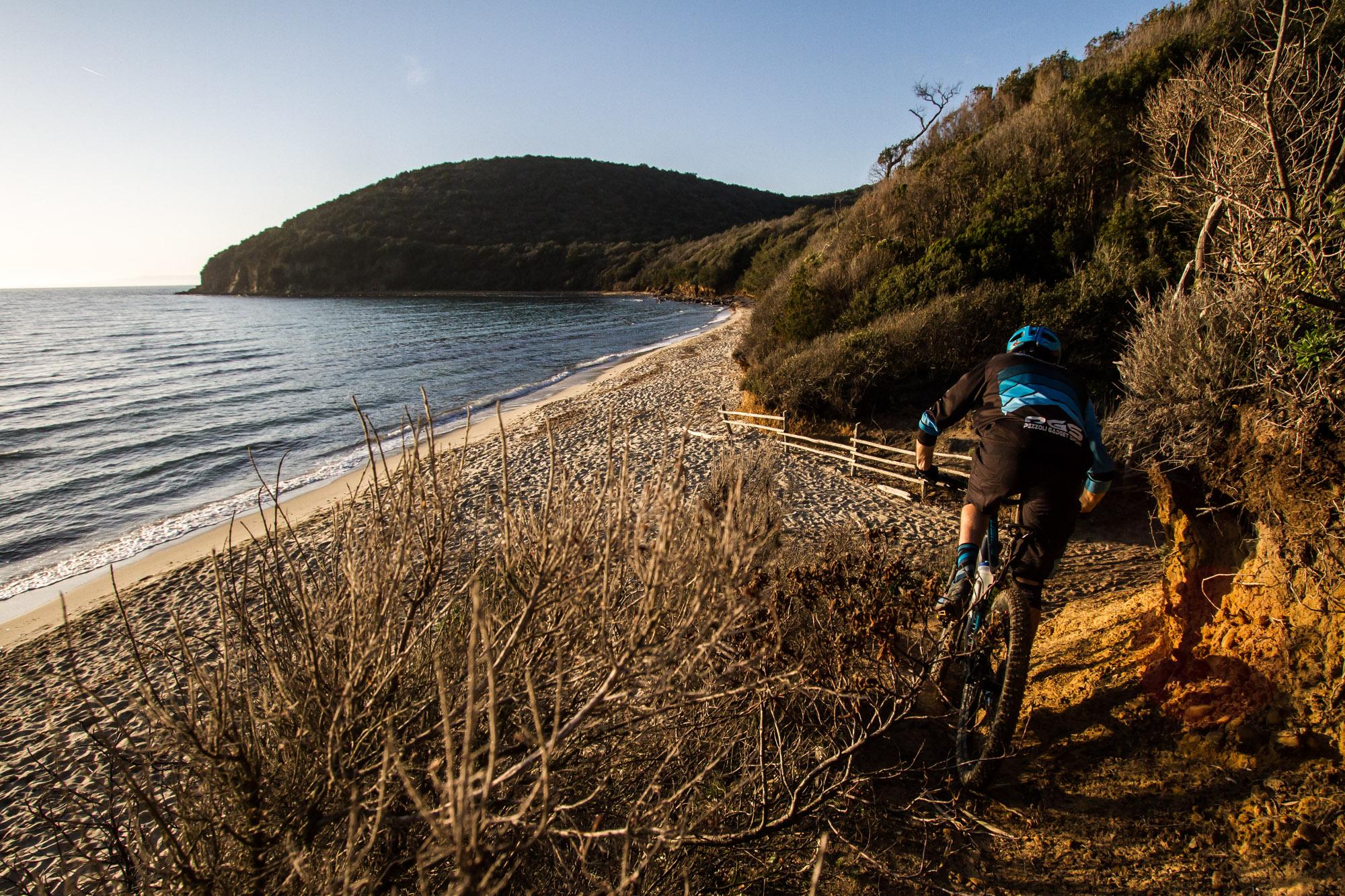 Giacomo Dodino termina il sentiero con un drop sulla spiaggiadi Cala Violina