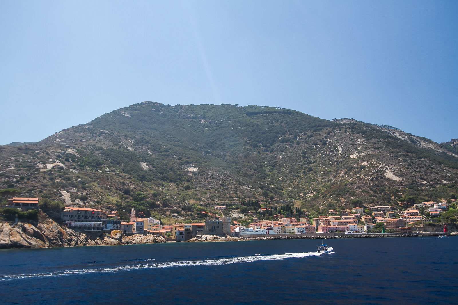 Giglio is also a contrasting place in strong summer light as the hillside rises behind the main port town.